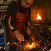 Blacksmith at anvil in forge at FireHouse Ironworks Ltd.